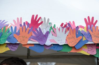 'Empowering Students to become allies, advocates, and agents for change' over student artwork, Multi-colored paper cut-outs of hands