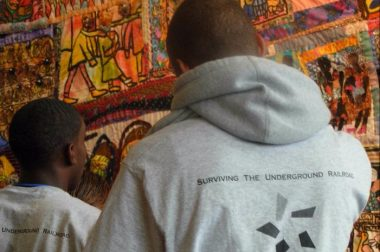 young men looking at the starr quilt
